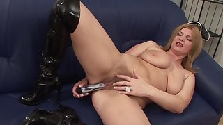 Busty mature cracks down her pussy with a big toy cock